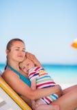 婴孩海滩sunbed的母亲放松 图库摄影