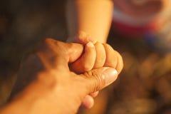 婴孩的手举行他的在日落时间的父亲的手 库存图片