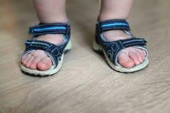 婴孩的被穿上鞋子的腿 儿童在他们的脚的` s凉鞋 小孩鞋子 最小的旅客的旅游凉鞋 新的购买 免版税库存图片