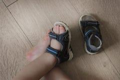 婴孩的被穿上鞋子的腿 儿童在他们的脚的` s凉鞋 小孩鞋子 最小的旅客的旅游凉鞋 新的购买 免版税库存照片