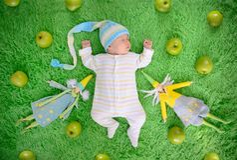 婴孩睡觉周围用绿色苹果和纺织品神仙 免版税图库摄影