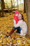 婴孩秋天女孩母亲年轻人 免版税库存图片