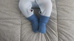婴孩移动在蓝色袜子穿戴的她的腿 r 股票录像