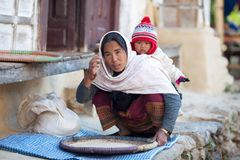 婴孩给国家农民妇女穿衣 库存照片