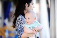 婴孩背景男孩前面她的藏品母亲微笑的查阅年轻人 免版税库存照片