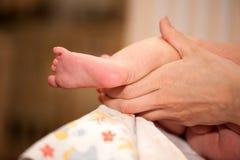 婴孩脚在母亲的手上在改变的桌上的 库存照片