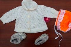 婴孩衣裳、赃物和soother在木背景 库存照片