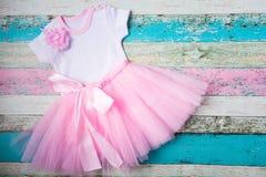 婴孩设置了-桃红色薄纱裙子、心脏白色紧身衣裤和在淡色木背景的一个美丽的桃红色头饰带 顶层 库存照片