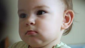 婴孩边射击特写镜头画象,严肃的被集中的小孩,听母亲 影视素材