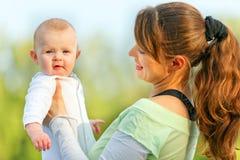 婴孩递藏品母亲微笑惊奇 免版税库存照片