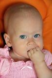 婴孩逗人喜爱拳头女孩吮 库存照片