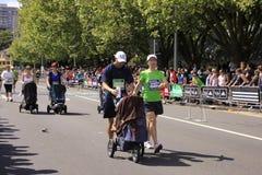 婴孩马拉松摇篮车种族婴儿推车 免版税库存照片