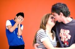 嫉妒夫妇拥抱的人 库存图片