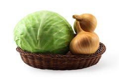 嫩卷心菜和金葱的头在篮子的 免版税库存照片