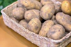 嫩土豆土豆顶视图在一个篮子的在灰色木背景 免版税库存照片