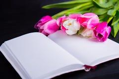 嫩桃红色郁金香和开放笔记本花束在黑木 库存照片