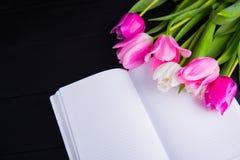 嫩桃红色郁金香和开放笔记本花束在黑木 免版税库存照片