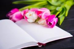 嫩桃红色郁金香和开放笔记本花束在黑木 图库摄影