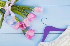 嫩桃红色郁金香和挂衣架花束与衣裳在蓝色wo 库存图片