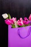 嫩桃红色郁金香花束在紫色购物袋的在黑wo 免版税库存照片