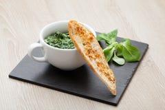 嫩煎的大蒜菠菜盘,与熔化che的被烘烤的面包切片 免版税库存照片