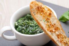 嫩煎的大蒜菠菜盘,与熔化che的被烘烤的面包切片 库存图片