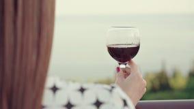 嫩红头发人女孩在酿酒厂大阳台站立,拿着一杯红葡萄酒 妇女饮料酒有在海的一个看法 股票视频