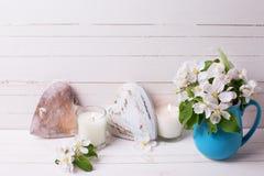 嫩苹果树开花,心脏和蜡烛在白色木ba 库存图片