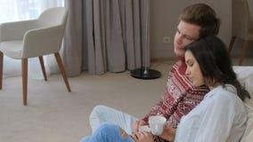 嫩镇静休闲坐在家的夫妇享用咖啡 股票录像