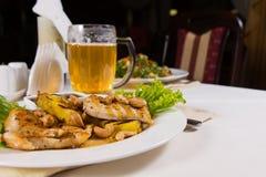 嫩水多的鸡肉盘和啤酒 免版税库存照片