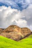嫩绿的绿色山和小山与蓝天和滚动的Clou 库存图片