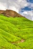 嫩绿的绿色山和小山与蓝天和滚动的Clou 免版税库存照片