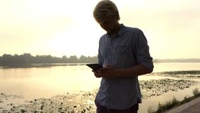 嬉戏人看他的智能手机并且对Dnipro微笑户外 股票录像