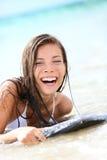 嬉戏冲浪板笑的妇女岸上-,湿 库存图片