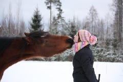 嬉戏地亲吻棕色马的美丽的少年女孩在冬天 免版税库存照片