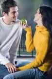 嬉戏地吃苹果的夫妇 免版税库存照片