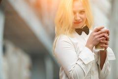 嬉戏地微笑和拿着咖啡的美丽的白肤金发的妇女画象  图库摄影