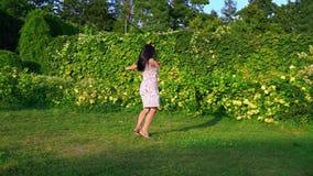 嬉戏地盘旋在她自己附近的少妇在一个绿色庭院里 一个微笑的浅黑肤色的男人的画象有起波纹的面颊的 影视素材