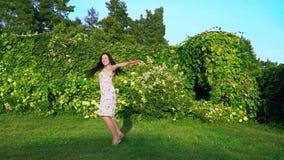 嬉戏地盘旋在她自己附近的少妇在一个绿色庭院里 一个微笑的浅黑肤色的男人的画象有起波纹的面颊的 股票录像