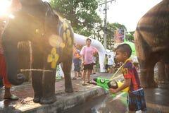 嬉戏地飞溅水乐趣和幸福的大象和男孩 库存照片