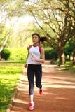 嬉戏女孩赛跑者在一个绿色夏天公园,健身训练 库存照片