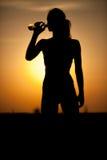 年轻嬉戏妇女饮用水的剪影 免版税库存图片