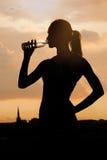 年轻嬉戏妇女饮用水的剪影 免版税库存照片