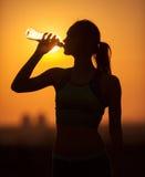 年轻嬉戏妇女饮用水的剪影 库存图片