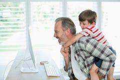嬉戏的在家研究计算机的父亲和儿子 免版税库存图片
