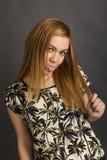 嬉戏的女孩画象开玩笑地伸出了她的舌头 图库摄影