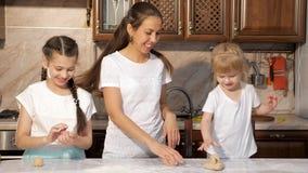 嬉戏的妈妈和两个女儿在一起抹上的厨房里一起烹调在面粉,乐趣时间 股票视频