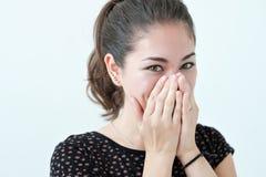 嬉戏的害羞的妇女掩藏的面孔用她的手 免版税库存图片