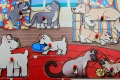 嬉戏的小狗老,破旧的儿童` s木难题和小猫 免版税图库摄影