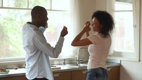 嬉戏的愉快的年轻非裔美国人的夫妇跳舞一起在厨房里 股票视频